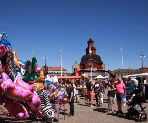Marknadsbild på rådhuset med blå himmel, människor och ballonger.