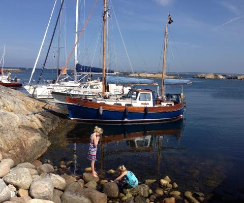 Två barn leker vid vattenbrynet vid en naturhamn i Kosterhavets nationalpark.