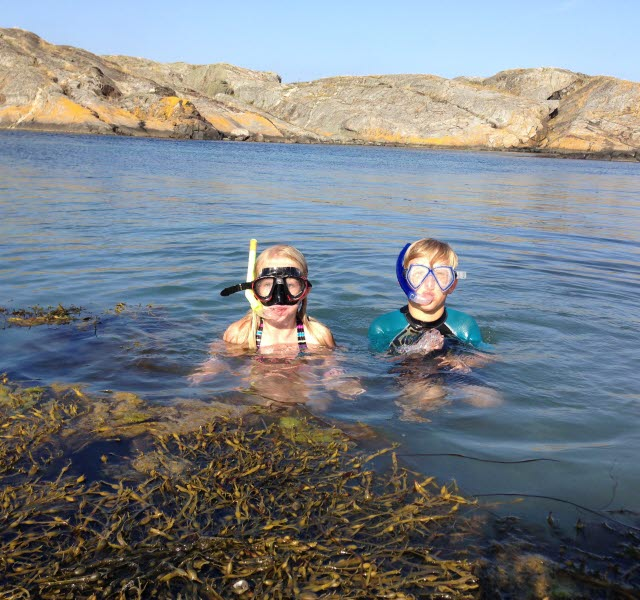 Two children are bathing in the sea and wearing snorkel equipment.