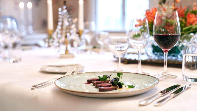 Närbild på fint dukat bord med en kötträtt och ett glas rött vin.