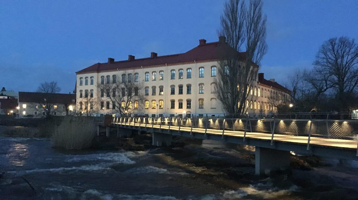 Universitetsbron över ån Tidan i Mariestad, med Trädgårdens skola i bakgrunden.