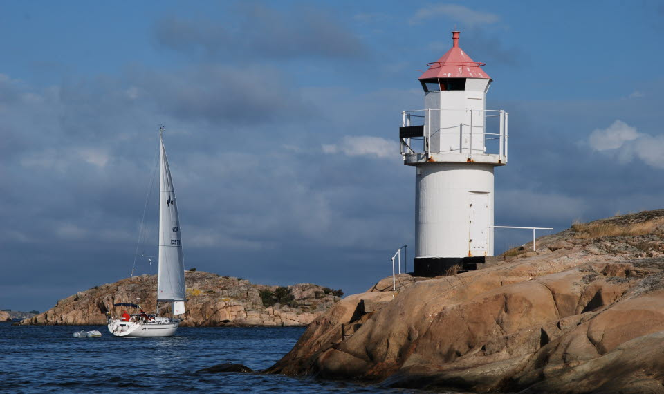 Vit segelbåt i Kosterhavet och till höger om båten står en vit fyr på klipphäll.