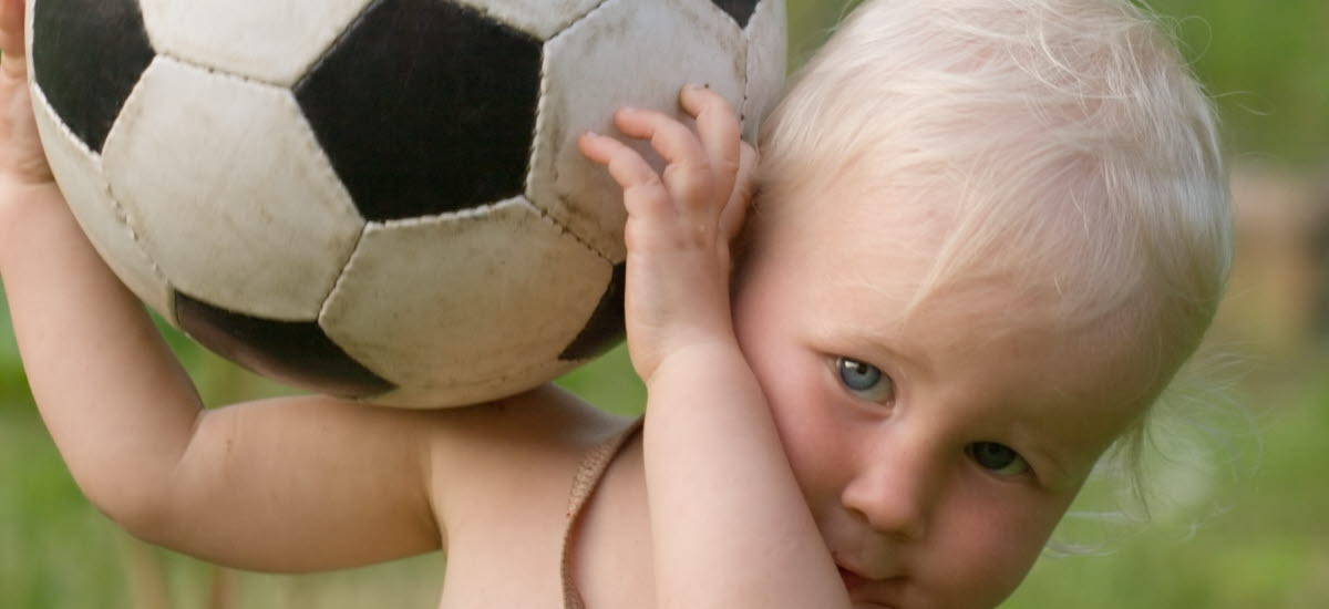 Ett litet barn håller en fotboll i händerna.