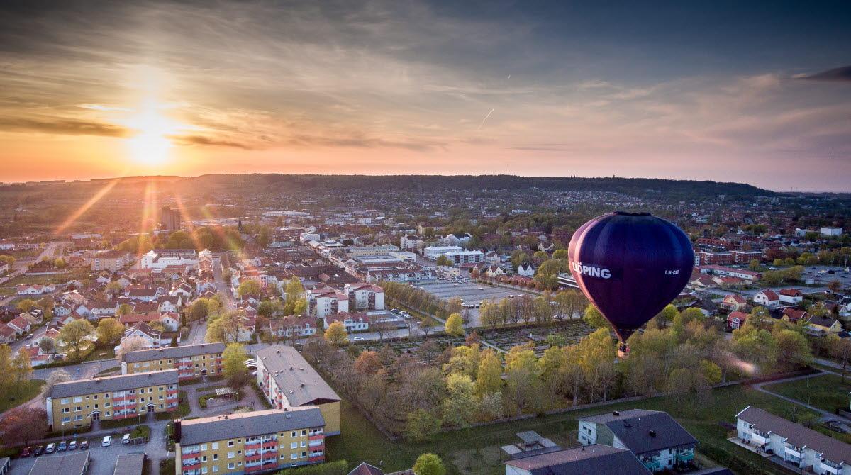 En svart luftballong med texten Falköping på flyger över staden.