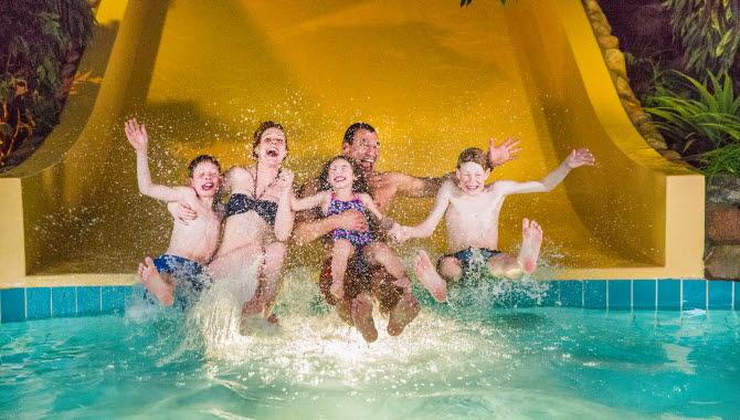 En familj som åker nedför en rutschkana på Arena badhus.