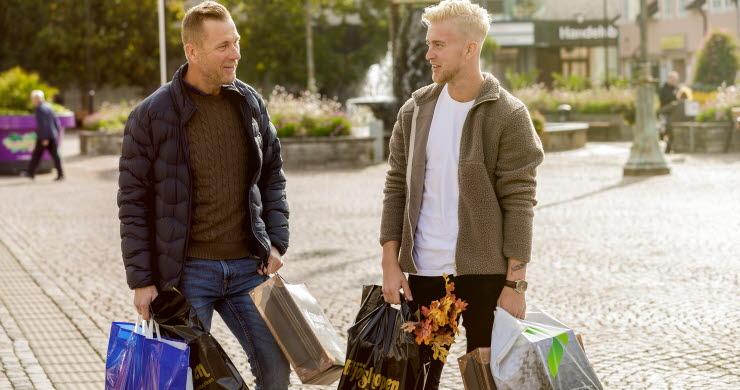 Två män står på torget med kassar i händerna.