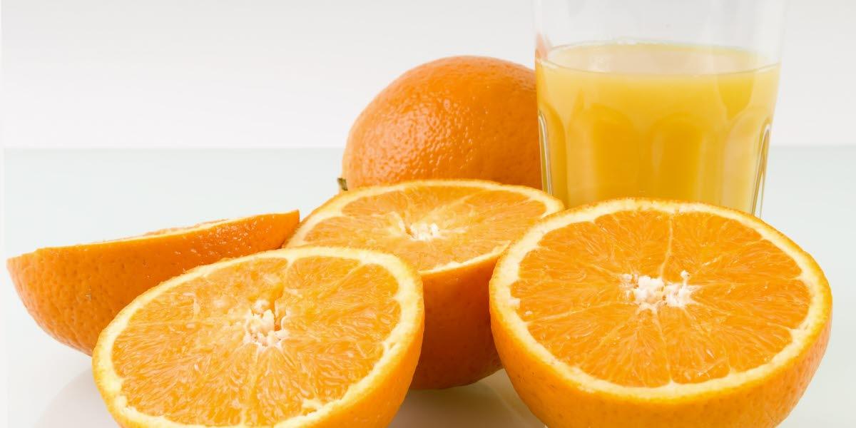Gula apelsinhalvor med ett glas juice.