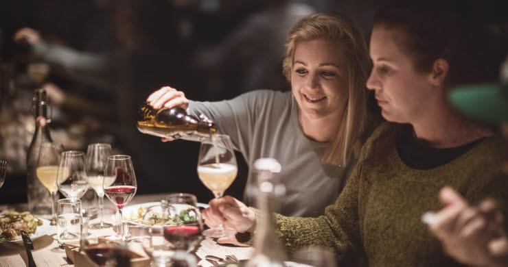 Kvinna fyller ett glas vid ett dukat bord