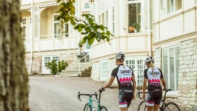 Kvinna och man som leder sina cyklar utan för Kurorten.
