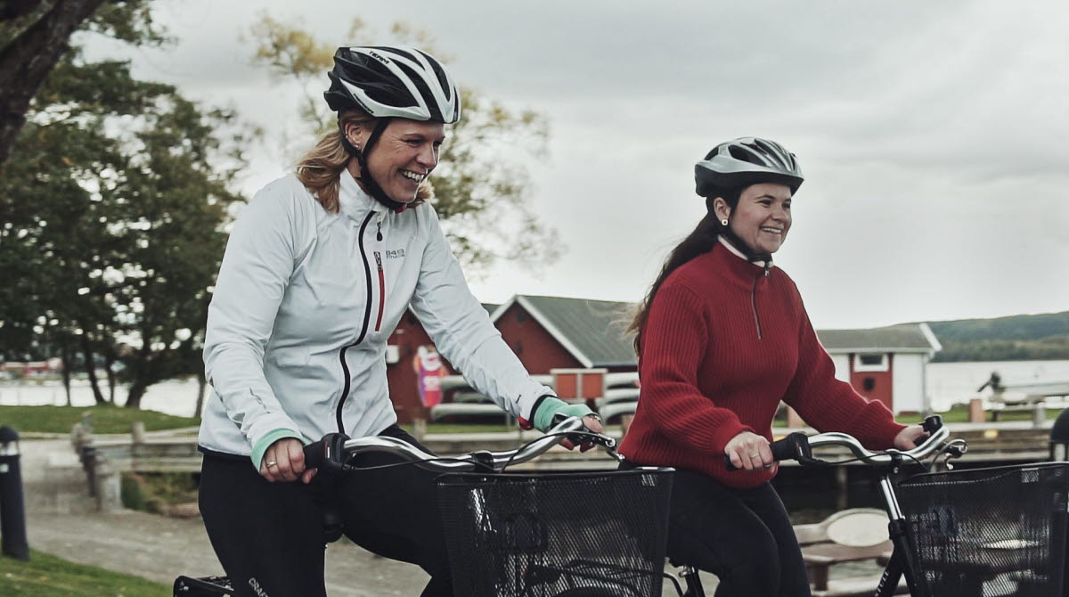 Två personer cyklar med en sjö i bakgrunden