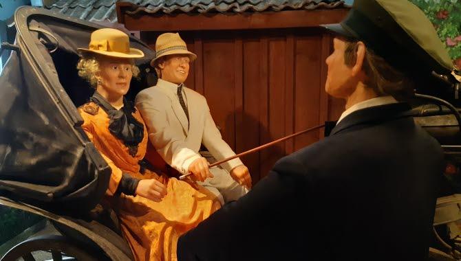 Ett par sitter i en vagn,  en man står framför i uniform.