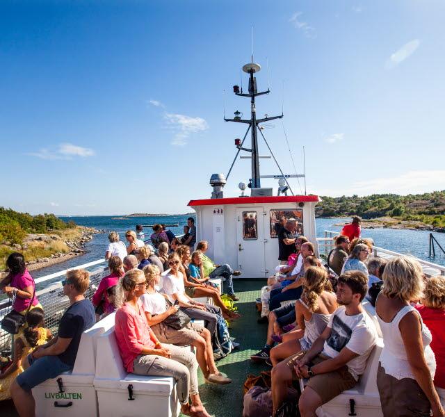 Människor sitter på övre däck på väg ut till Kosteröarna med Kosterbåten.