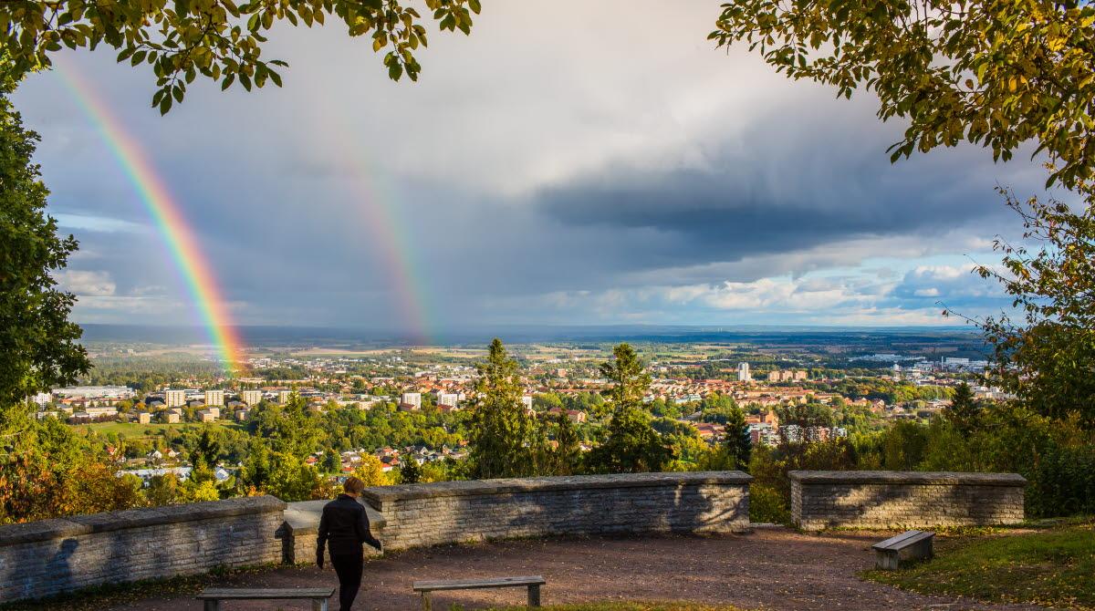 En kvinna går vid utsiktsplatsen på platåberget billingen. På himlen syns två regnbågar.