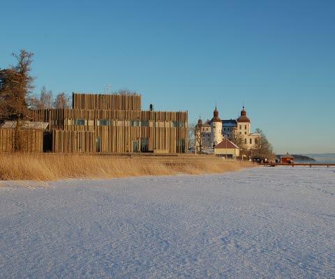 Naturum Vänerskärgården - Victoriahuset med Läckö Slott vid sidan om. Framför ligger Vänern som är täckt av snö och is.