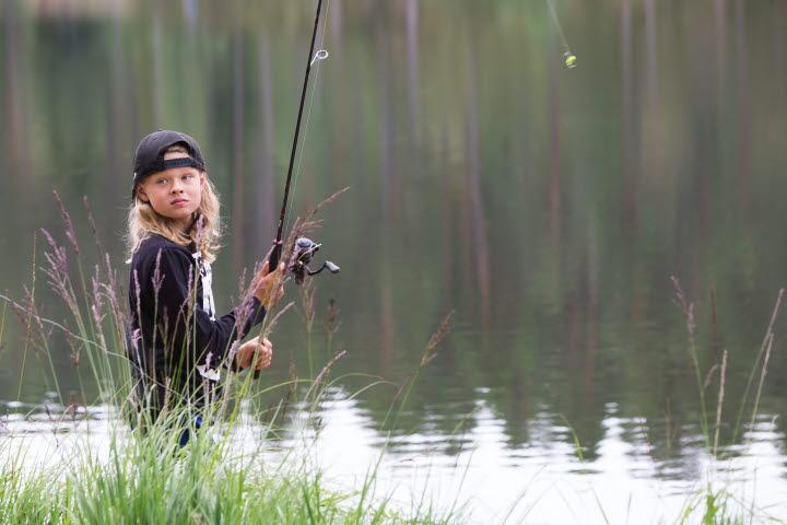 Ett barn står och fiskar vid en sjö.