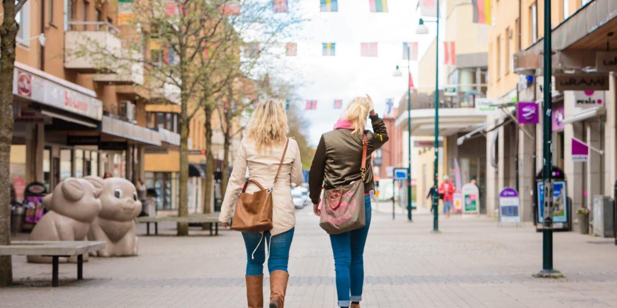"""Två kvinnor går bort från kameran på en tom gata. I luften hänger flera flaggspel och till vänster syns ett konstverket """"Piglets""""."""