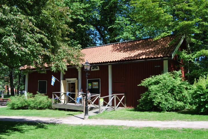 Kulturmagasinet på Turbinhusön i Tidaholm. En röd liten trästuga med vita knutar.