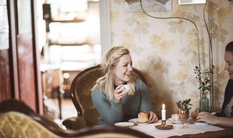 Kvinna fikar på kanelbulle och kaffe