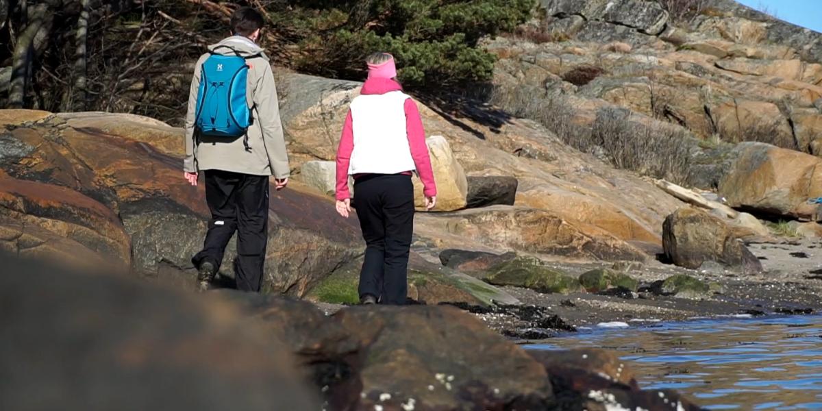 Två personer vandrar längst en klippig strand på Nötholmen.