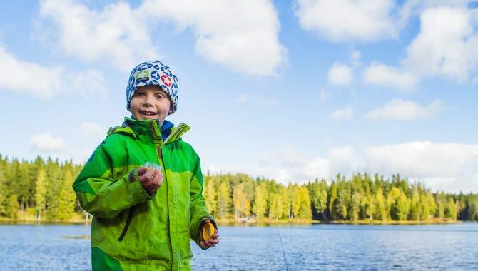 Ett barn i knallgrön jacka står med en burk fiskbete i handen. I bakgrunden glänser Hållsdammens vatten i solen.