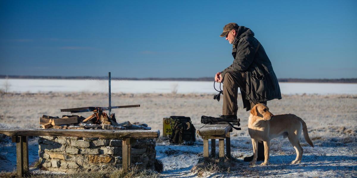 Man som står vid en grillplats med sig hund. Blå himmel i bakgrunden.
