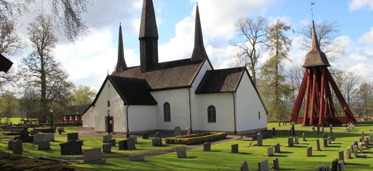 Kungslena kyrka. En vit stenkyrka med röd träklockstapel vid sidan.