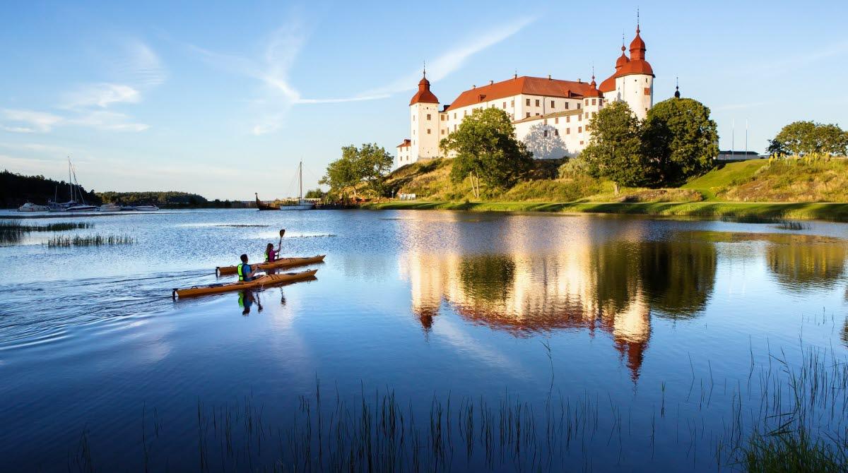 Två personer paddlar kajak med Läckö Slott i bakgrunden.