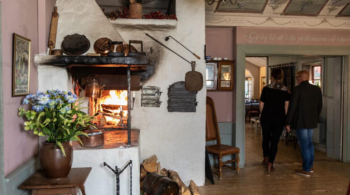 Två personer som går in i matsalen på Cesarstugan en eld brinner i öppna spisen.