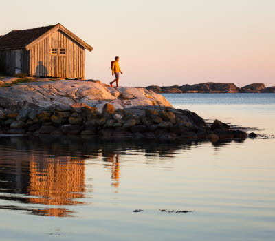 A person is standing on a cliff in front of a old and grey boathouse at South Koster. The ocean is calm and the sun is about to set.