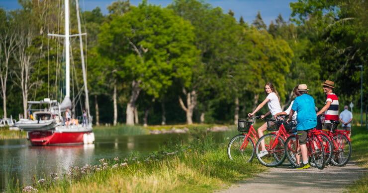 Tre personer stå med sina cyklar på kanalbanken och tittar på en segelbåt i Göta kanal.