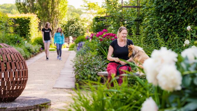 En slottsträdgård med blommor och en promenadgång omgiven av perenner. Två barn promenerar i bakgrunden och en kvinna sitter på en bänk och pratar med sin hund.