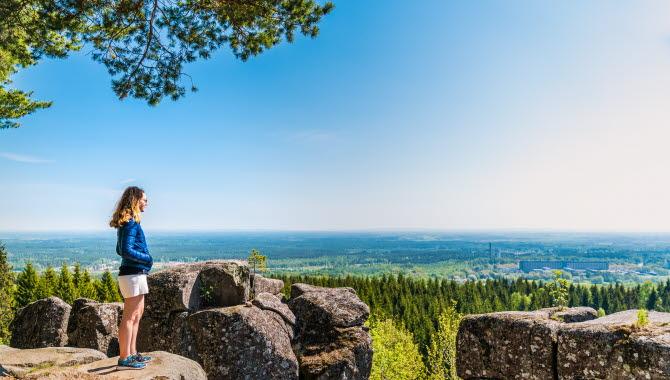 Ung kvinna står vid kanten av de stora diabaspelarna vid Ryds grottor och njuter av den blåa himmelen och den vackra utsikten.