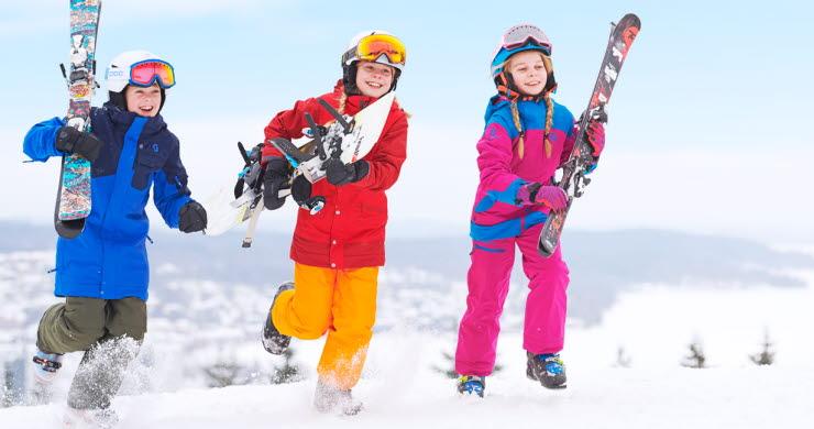 Tre barn i färgglada kläder med skidor i famnen springer på toppen av Ulricehamn Ski Center.