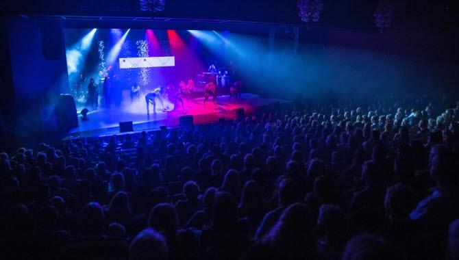 En mörk bild visar ett publikhav tom tittar mot en scen. På scenen syns tio personer som lyses upp av blått och rött ljus. De dansar, och i bakgrunden står en kör.