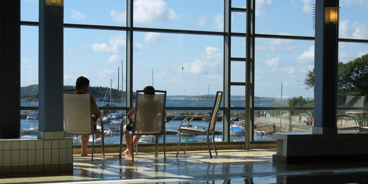 Två personer sitter inne på Strömstad Badanstalt och tittar ut över den södra hamnen.