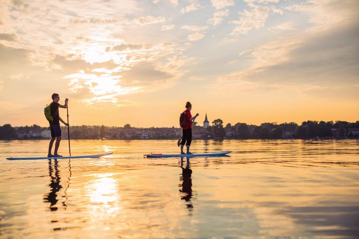 Two people are slowly paddling on a Stand up paddleboard on lake Vättern.