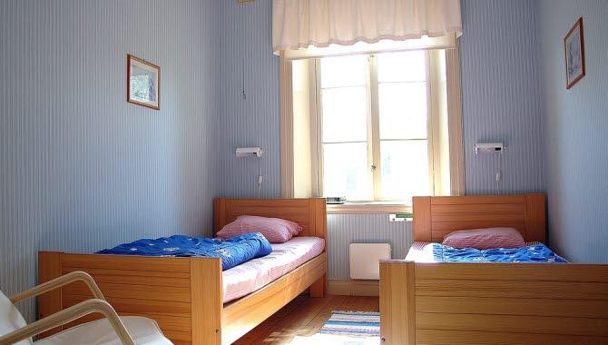 Två enkelsängar i ett blått rum på ett vandrarhem.