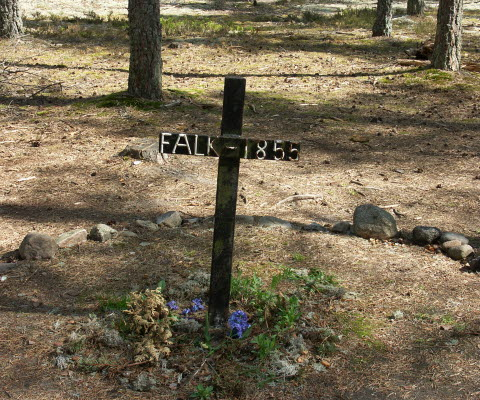 Falks grav som finns i en skog på Hökensås naturområde. Ett träkors med stenar runtom.