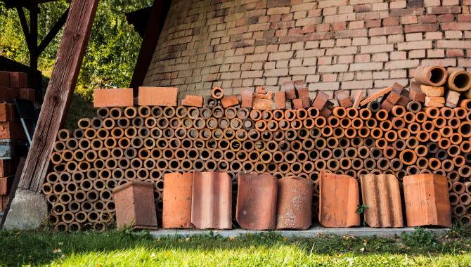 En närbild på tegelrör som är tillverkade på Horns tegelbruk. De ligger uppradade mot väggen på tegelbruket.
