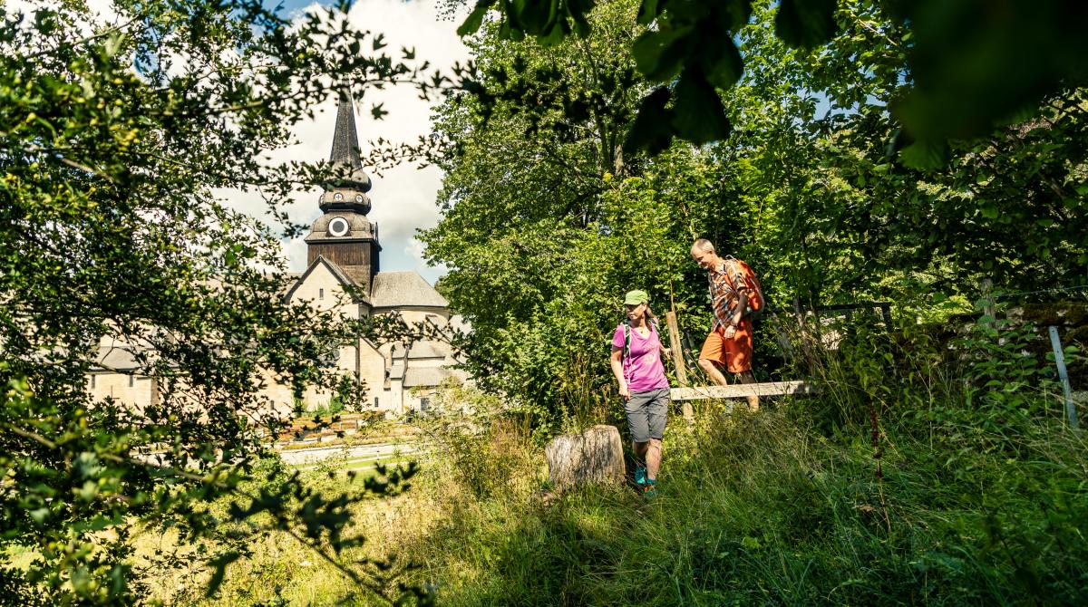 Man och kvinna som vandrar i gröngräset med Varnhems klosterkyrka i bakgrunden.