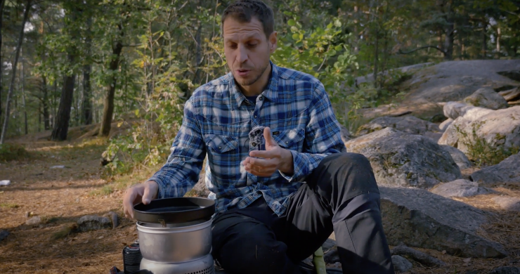 En man i blårutig skjorta visar hur man använder ett trangiakök