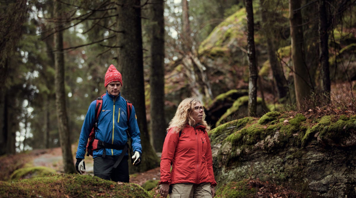 Två vandrare i färgglada kläder går genom en vacker skog