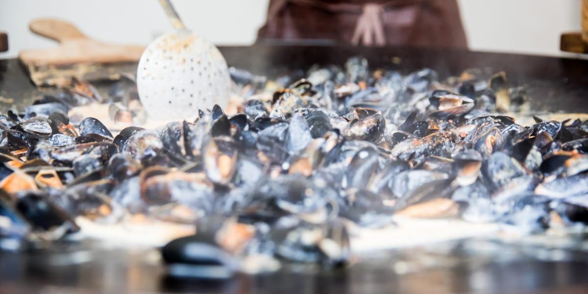 Matiga musslor förbereds på muurikka i samband med utomhusmatlagning i Falkenberg.