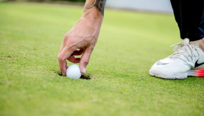 Hand plockar upp en golfboll ur hålet på en green.