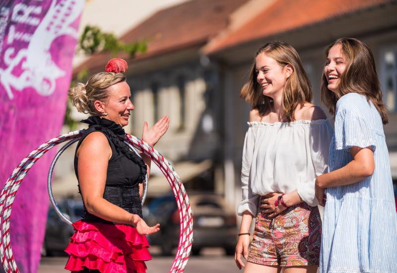 Uppträdande artist står och pratar med besökare vid festival på torget i Hjo.