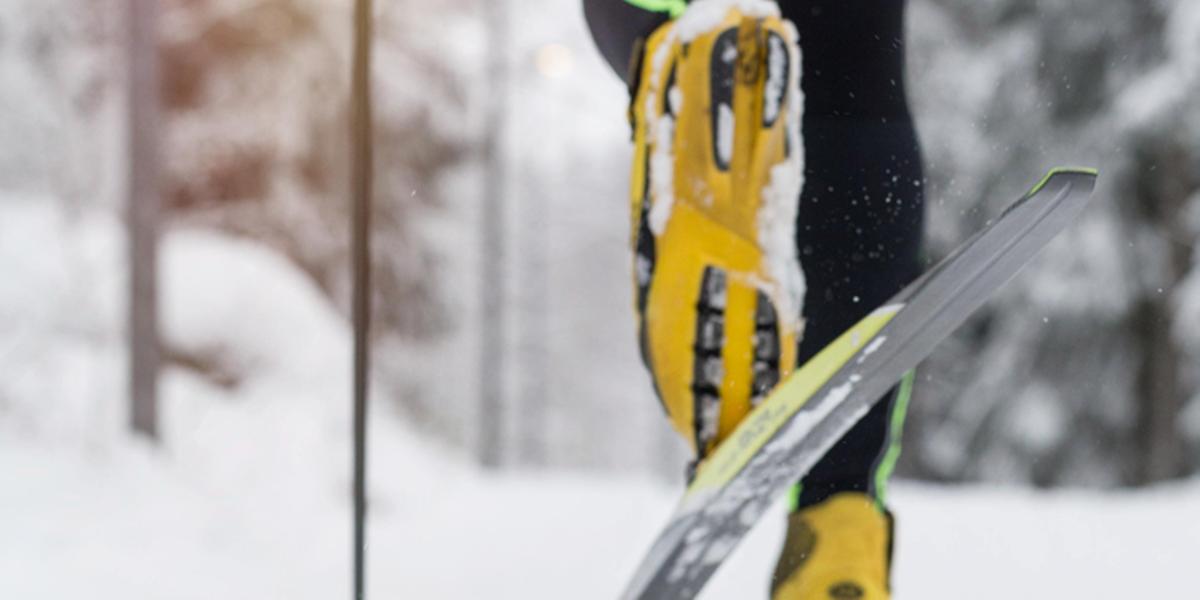 Vinter och snörikt. Närbild på längdskidåkare bakifrån, du ser ena skidan och pjäxan underifrån när åkaren glider fram i spåret på andra skidan.