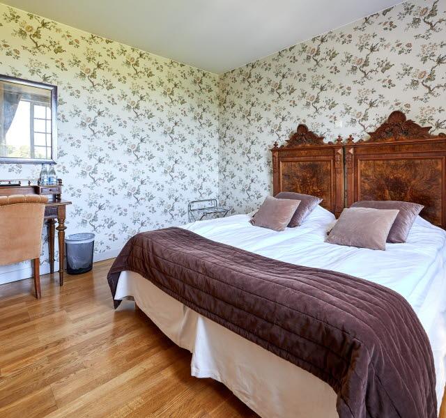 Hotellrum där dubbelsängen står i fokus. Hög sänggavel i trä, lila kuddar och överkast samt vita sängkläder. Tapeten är blommig och till vänster om sängen står ett litet bord med en lampa och en spegel på väggen