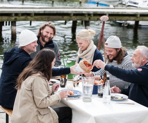 People sitting around a set table and eat seafood on a  boat dock.