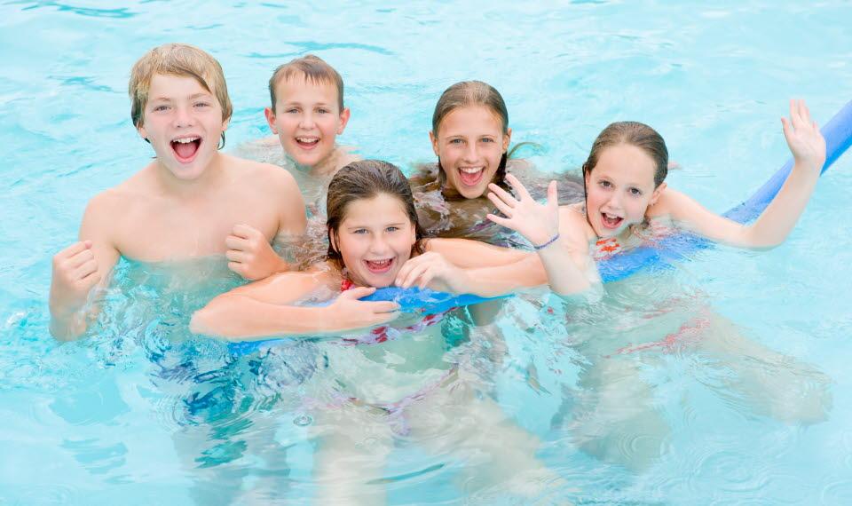 Fem ungdomar i en pool som leker och skrattar