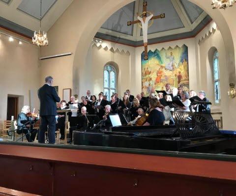 Mariestads kammarkör med dirigent uppträder i en kyrka.